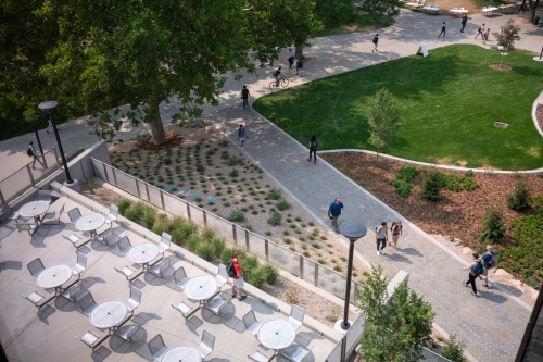 A view of the west pathway and outdoor seating area of the Carolyn and Kem Gardner Commons. The pathway shown leads to the A. Ray Olpin Union Building.